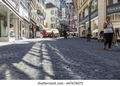 Lausanne, Switzerland - July 19, 2016: Street view in the old town with shops, people walking and an outdoor cafe. Lausanne is the capital city of the Canton of Vaud.