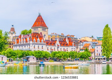 LAUSANNE,  SWITZERLAND, JULY 19, 2017: People are enjoying a sunny day in front of the Chateau d'Ouchy hotel at Lausanne, Switzerland