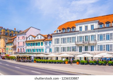 LAUSANNE,  SWITZERLAND, JULY 19, 2017: People enjoying a sunny day in cafes inside of hotels on lakeside of Gevena lake at Lausanne, Switzerland