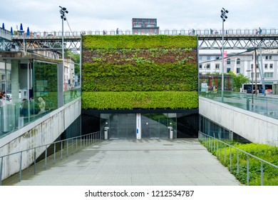LAUSANNE, SWITZERLAND - MAI 23, 2018 : Modern and beautiful entrance to the Flon metro station in Lausanne, Switzerland. A wall of plants and walk bridge above the entrance.