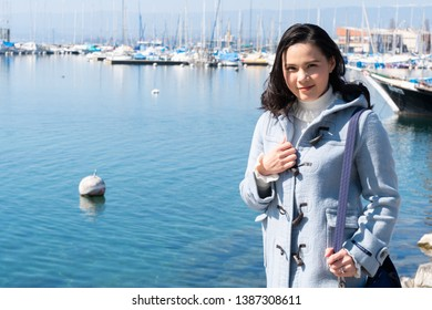 Lausanne, Switzerland - March 24, 2019 : Asian woman at private yachts docked in Lausanne Ouchy port, Switzerland on Lake Leman (Geneva Lake) on sunny winter day.