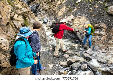 Lauterbrunnen, Switzerland - 9/6/2014:  Hikers on the Eiger trail in the Alps mountains above Lauterbrunnen.  A man is assisting a woman in a small stream crossing.