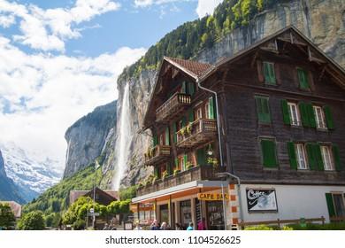 LAUTERBRUNNEN, SWITZERLAND : MAY 20, 2018 - Building in Lauterbrunnen town with Staubach Waterfall in background.