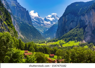 Lauterbrunnen valley, waterfall and the Lauterbrunnen Wall in Swiss Alps, Switzerland. Eiger, Monch and Jungfrau mountains in the background.