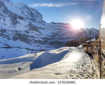Lauterbrunnen,Switzerland - January 1,2019 : Yellow train has passengers and running in on railway tracks with snow and sunshine in winter to go to theLauterbrunnen at Switzerland.