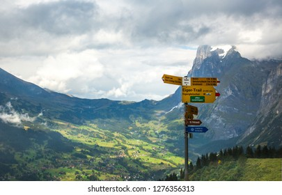 Lauterebrunnen, Switzerland - 9/8/2014:  A trail sign on the Eiger trail in the Alps mountains above Lauterbrunnen, Switzerland.  The village of Grindelwald is in the background.