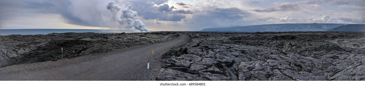Lava Delta and active smoking lava flow in a lava rock desert In Hawaii, Big Island with road in the middle - Kamokuna Ocean Entry Volcano National Park
