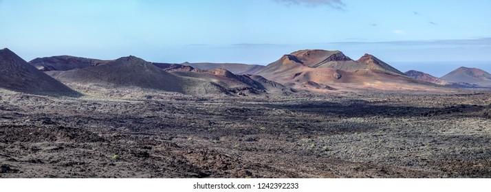Lava field with volcano caldera. Timanfaya national park, Lanzarote, Canary Islands. Panorama background.