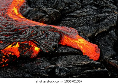 "A lava flow emerges from a rock column and pours into a black volcanic landscape, the hot lava shows up in yellow and red shades - Location: Hawaii, Big Island, volcano ""Kilauea"""