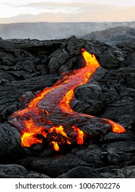 "A lava flow emerges from a rock column and pours into a black volcanic landscape, in the background the first daylight - Location: Hawaii, Big Island, volcano ""Kilauea"""