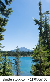 Lava Lake, along the Cascade Lakes Scenic Byway near Bend Oregon, with Mt. Bachelor in the background. Negative space, framed by trees
