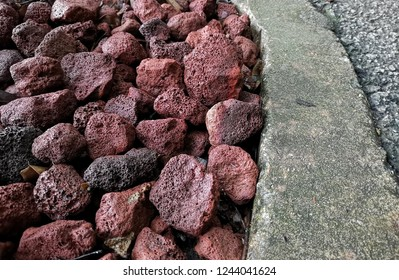 The lava rocks in parks placed along edge of walkway are an igneous rocks which are also meant hardened lava. It is a volcanic rock, and landscaping lava rock is a kind of rock known as obsidian.