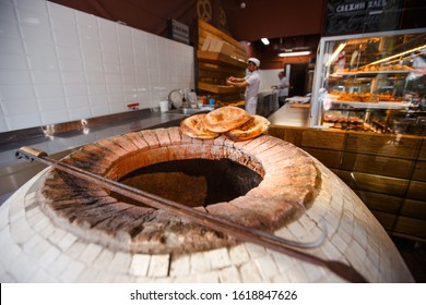 Lavash, flat unleavened white bread in the form of a thin flatbread made of wheat flour, is baked in an oven , in a tandoor. Ready pita bread lies on the edge of the oven. The furnace is in the shop,