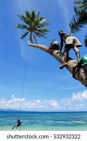 LAVENA, FIJI - NOVEMBER 27: Unidentified kids swing on a rope swing on November 27, 2013 in Lavena village on Teveuni island, Fiji. Taveuni is the third largest island in Fiji.