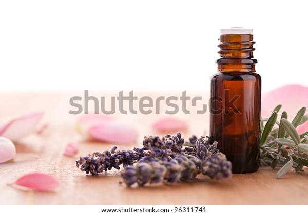 lavendel and parfum bottle with rose leafs on wooden background
