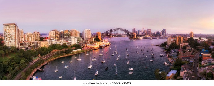 Lavender bay on Sydney Harbour off North shore in view of The Rocks and major Sydney city landmarks in wide aerial panorama at sunset with bright illumination.