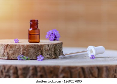 lavender essential oil in a brown glass bottle and fresh lavender flowers on natural background