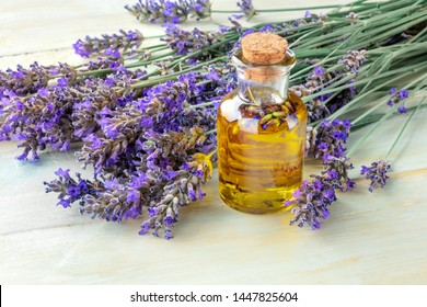 Lavender essential oil with lavender flowers on a rustic wooden background with copyspace. A glass bottle with a cork with buds infusing