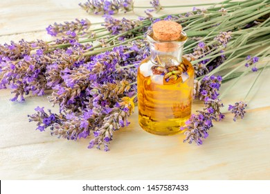 Lavender essential oil in a glass bottle with a bouquet of fresh blooming lavender flowers on a rustic wooden background with a place for text, toned image
