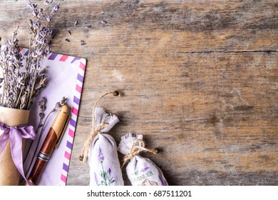 Lavender flowers in an antique scoop and lavender bouquet on wooden background. Top view.