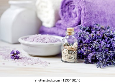 Lavender flowers, aromatic sea salt and towels. Concept for spa, beauty and health salon, cosmetics store. Natural cosmetics. Close up photo on white wooden background.
