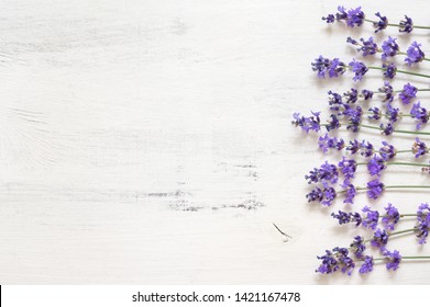 Lavender flowers as border on rustic shabby white wood background. Top view.