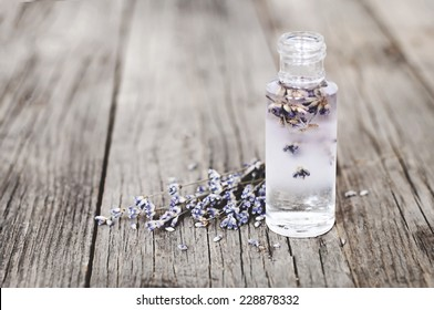 Lavender flowers and glass bottles on a wooden surface with natural light