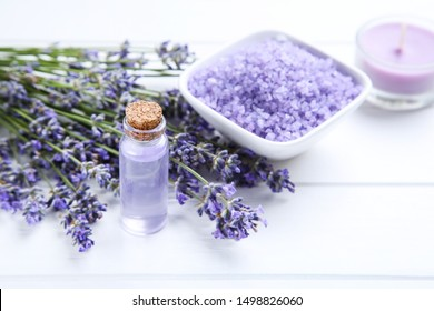 Lavender flowers with oil in bottle and salt in bowl on white wooden table