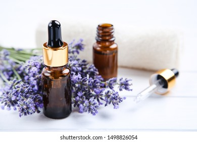 Lavender flowers with oil in bottles and towel on white wooden table