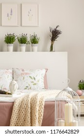 Lavender flowers on bedhead of bed with blanket in bright bedroom interior with candles and posters. Real photo