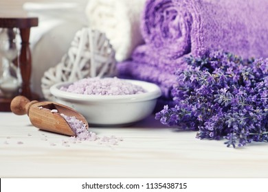 Lavender flowers, lavender soap, aromatic sea salt and towels. Natural skin care. Spa kit for beauty and health on white wooden background. Selective focus, close up