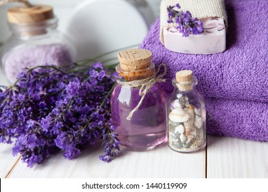 Lavender flowers, lavender soap, aromatic sea salt and towels. Concept for spa, beauty and health salon, cosmetics store. Close up photo on white wooden background.