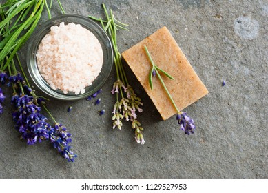 lavender flowers and soap samples, bath salt on basalt stone background