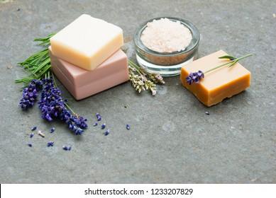 lavender flowers and soap samples, bath salt on basalt stone background