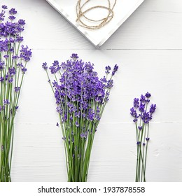 Lavender flowers and tray on white wooden table, flat lay. Bouquets of natural provence lavender herb plant, top view