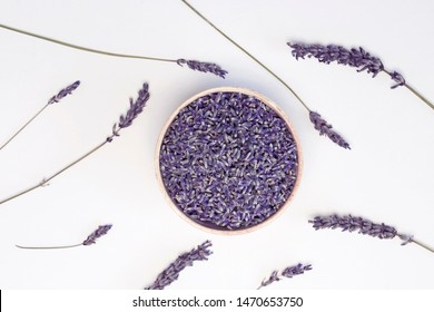 Lavender flowers in wooden plate and branches on white background, toned. Invitation, spa, recipe concept. Top view, close-up, flat lay, copy space, layout design