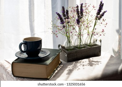 Lavender & Gypsophilia in bright sunlight on a table near a window, with a cup and a book.