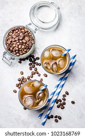 Lavender honey iced coffee in glass and coffee beans in glass jar on white background. Top view, copy space.