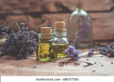 Lavender oil with fresh flowers on wooden background