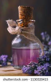 Lavender oil in a glass vial close-up on a wooden table