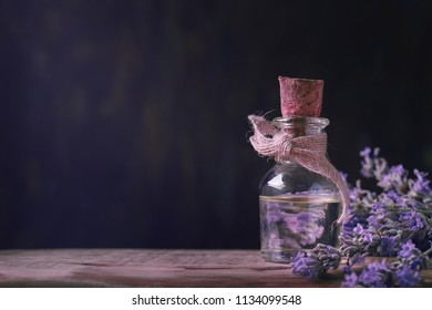 Lavender oil in glass vial close-up on a wooden table with space for text