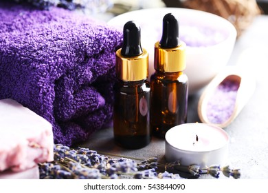 Lavender oil with soap and flowers on grey table