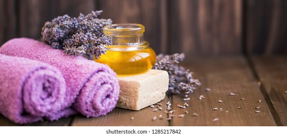 Lavender oil, towels, natural soap and lavender flowers on wooden background, lavender spa still life setting