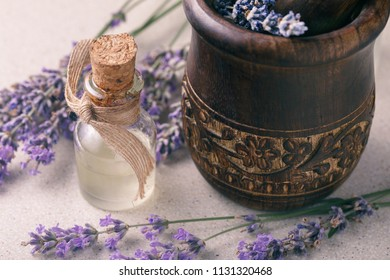 Lavender oil in a transparent bottle with flowers and a mortar for grinding the ingredients