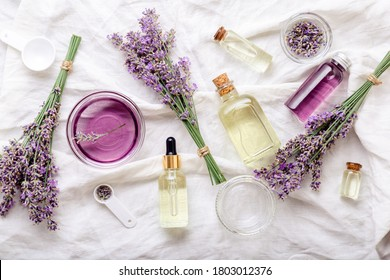 Lavender oils serum and lavender flowers on white fabric. Skincare cosmetics products. Set natural spa beauty products. Lavender essential oil, serum, body butter, massage oil, liquid. Flat lay - Shutterstock ID 1803012376