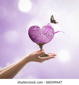 Lavender purple ribbon all kind of cancer awareness on heart tree with butterfly on volunteer's hand for medical charity campaign concept