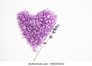 Lavender salt for spa treatments in the shape of a heart on a white background with a branch of natural lavender. Skin care concept. Flat lay.