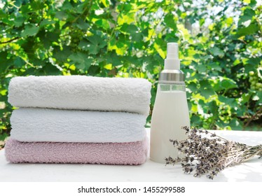 Lavender scent fabric softener.Stack of towels, softener and lavender on the white table against green leaves