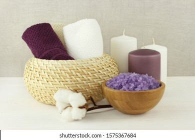 Lavender sea salt for bath in a bamboo bowl, cotton towels in a wicker vase and candles stand on a white wooden table against a gray wall