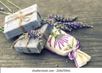 lavender soap and scented sachets with fresh flowers over wooden background. selective focus